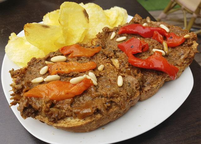 Tostada de morcilla vegetal con pimientos rojos asados y piñones